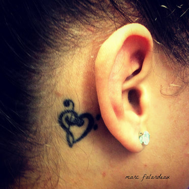 female ear and heart tattoo next to it