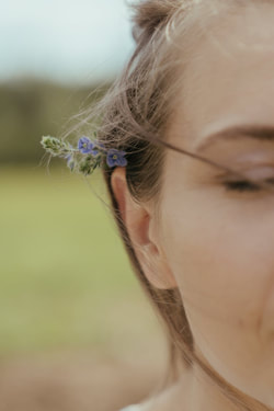 woman's ear with flowers behind it, eyes closed, spiritual