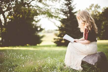 woman sitting on grass with book journal